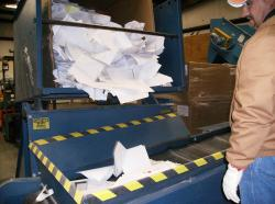 Aggie Recycling employee inspects paper before it is bailed
